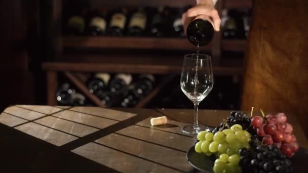 A közeli portré ömlött a fehér bor a pohárba, a háttérben a polcok tele a bor somiellier. A színes graped, a fekete nyomólapra összetétele.