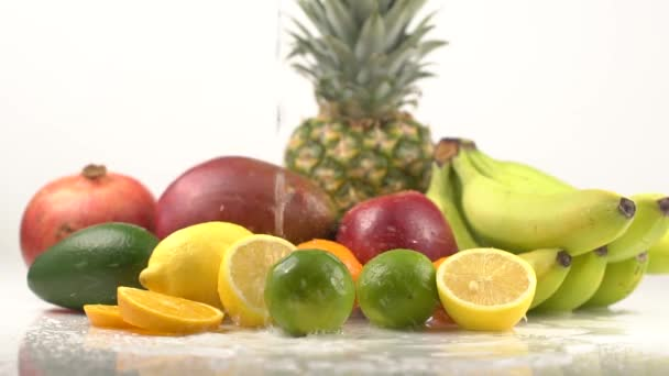 Water pours of exotic fruits lying on white table