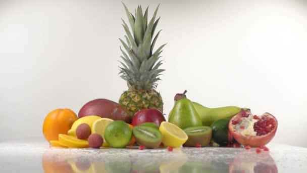 Kousky granátového jablka padají na stůl s exotickým ovocem
