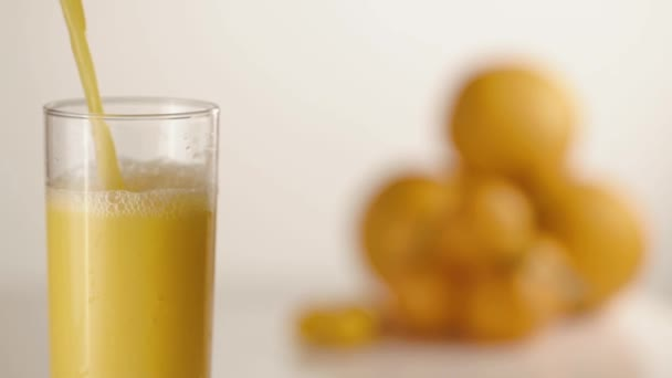 Juice pours in glass on table with oranges and mandarines