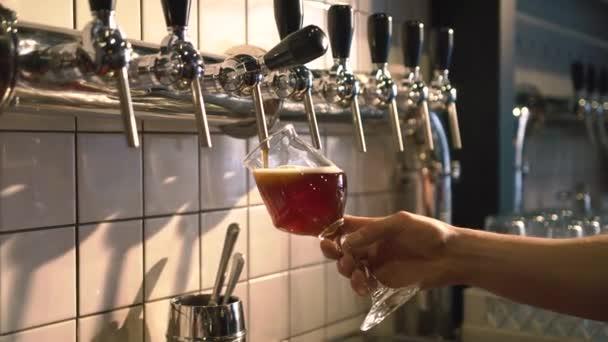 A csapos a világos sör özönlenek az üveg, a tervezet sör torony segítségével a kocsmában. Közelkép Fotó.