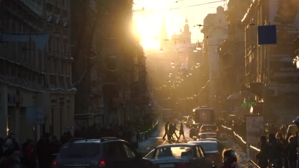 The view of the city centre landscape crowded with people, cars and trambuses during the sunset.