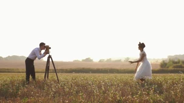 die reizende Komposition des Bräutigams beim Fotografieren der springenden Braut im Hintergrund des Frühlingsfeldes.
