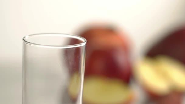 Červený nápoj je lití do prázdné sklenice na pozadí rozmazané ovoce. Detailní zobrazení
