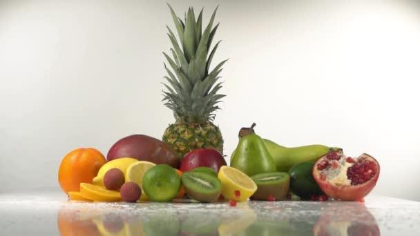 A gránátalma magokat bukása az asztalra és alma, kiwi, ananász, bogyók, citrom.