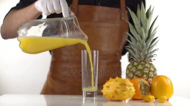 The man is pouring the orange juice from the decanter into the high glass placed near pineapple, persimmons and kiwano.