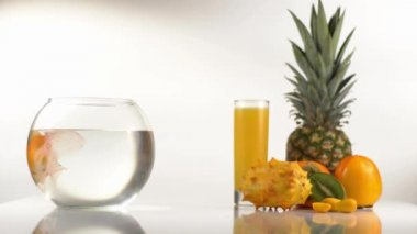 The golden fish in the round aquarium is placed near the glass with juice and food composition consisted of the pineapple, persimmons and kiwano.