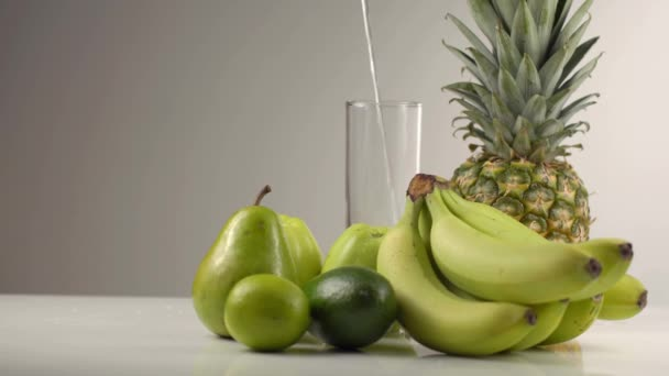 Rychlé padající vody do vysoké sklenice za zelené složení se skládala z jablka, banány, ananas a avokádo