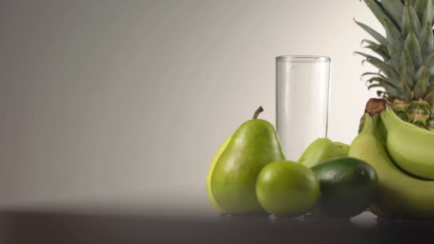 The part of the green fruit composition of the bananas, pineapple, apples, pears and avocado while the high glass becoming full with the water.