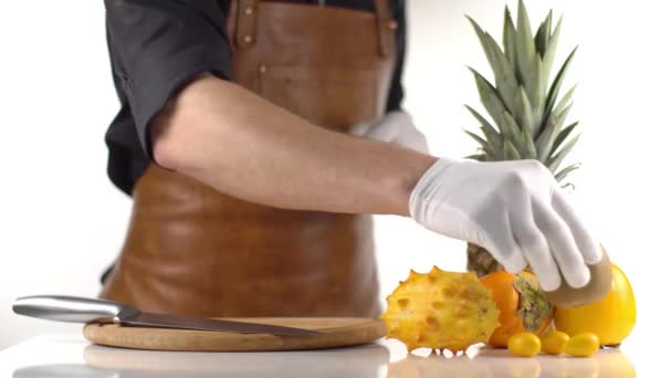 The orange tropical fruit composition consisted of pineapple, kiwano and persimmons. The cooker is cutting the tasty kiwi.