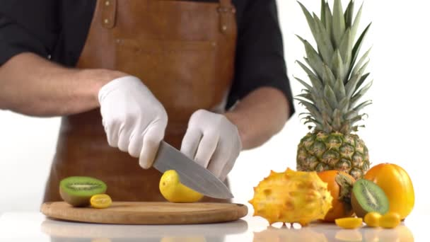 The man is cutting the lemon into slices on the wooden board placed near the pineapple, persimmons and kiwano.