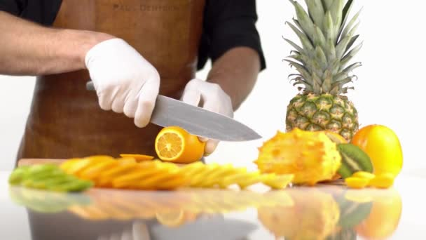 The composition of cut in slices orange fruits placed near the kiwano, persimmons and pineapple. The cooker is cutting the orange.