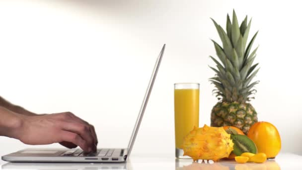 The close-up side view of the man typing on the laptop placed next to the pineapple, persimmons, kiwano and orange juice in the studio.