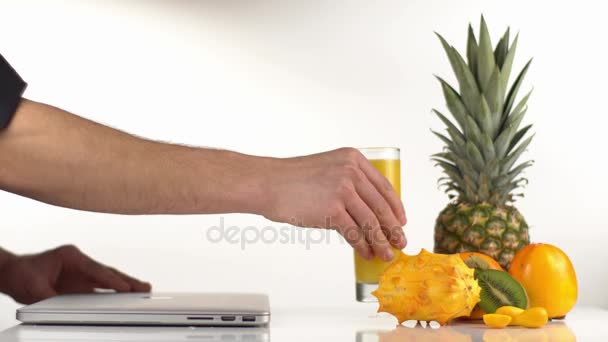 The close-up side view of the man drinking orange juice and opening the laptop. The glass ia placed near the orange composition consisted of the pineapple, persimmons and kiwano.