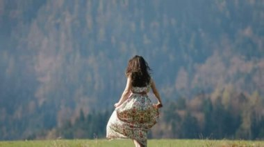 The close-up horizontal view of the girl in the long dress enjoying the free time in the mountains in spring.