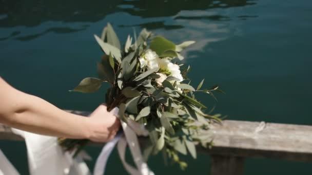 La mano sta tenendo che il bouquet ha consistito dei fiori di campo bianco e foglie di alloro - La mano sullo specchio ...