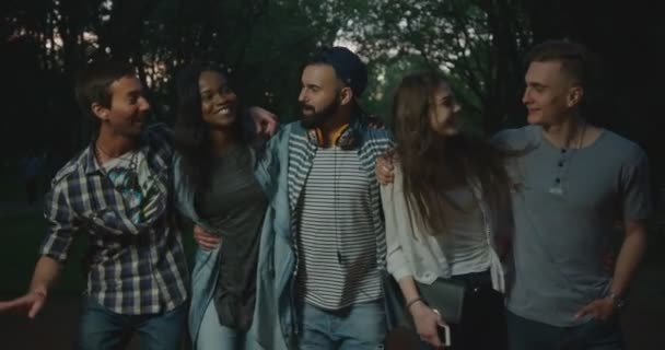 The close-up view of the five multicultural hipster friends are laughing and hugging during their walk in the evening park.