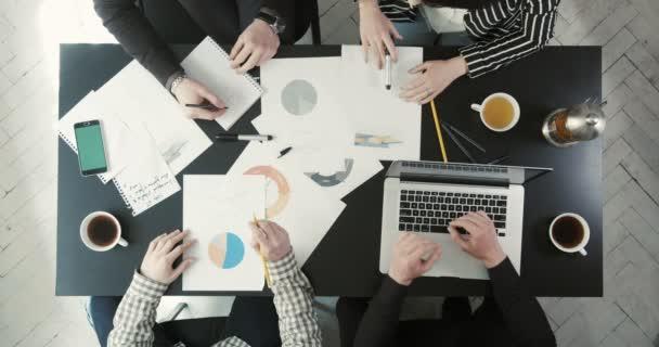 die Diskussion von vier Geschäftsleuten, die das Geschäftsproblem mithilfe von Grafiken, Zeitplänen und Laptops lösen sollen. die obige Ansicht der Zeiger mit Grafiken.