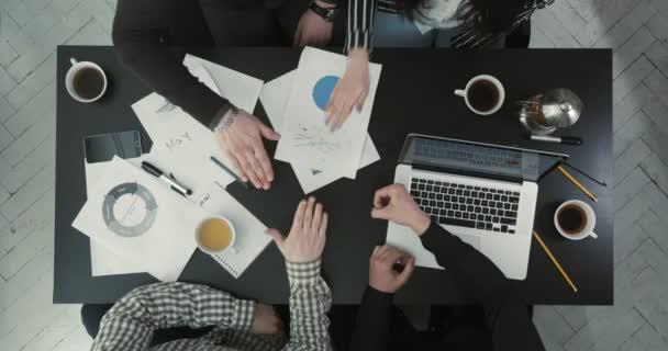 die obige Ansicht der Teamarbeiter, die die Stein-Papier-Schere spielen. Der Tisch ist mit Business-Grafiken und Laptop bedeckt.