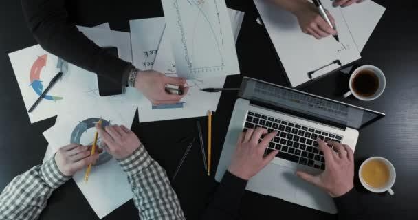 Detail nad zobrazením rukou podnikatelů psaní na notebooku, zobrazující grafiku a psaní plánu v poznámkovém bloku.