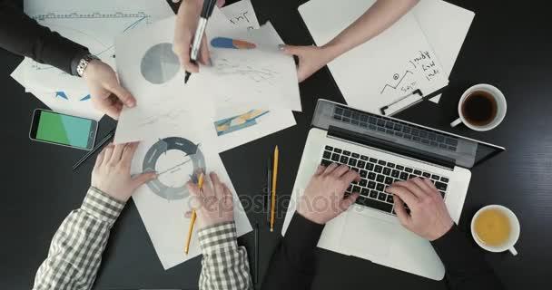 Kezében az üzletemberek tartja a grafika, a laptop gépelés. A fenti nézet üzleti összetétele közelről.