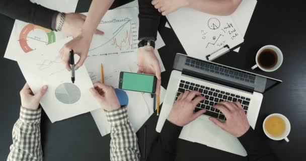 Výše uvedené pohled ruky zobrazení obrazovky mobilního telefonu podnikatelům diskutovat o problému pomocí grafiky a laptop.