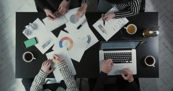 Výše uvedené pohled týmu pracují na základě obchodních problémů pomocí grafiky a laptop. Žena se dohadovat s mužem.