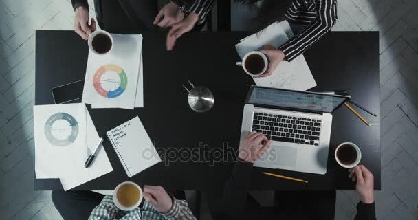 Výše uvedené zobrazení týmu, zatímco sedí u stolu pití čaje pokryté obchodní grafiku, plány a notebook.