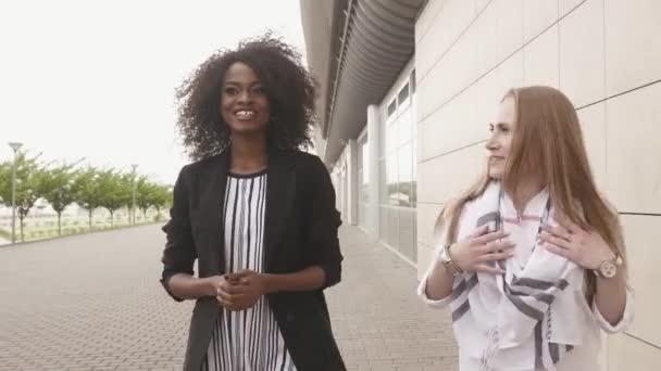 Due corsa mixed giovani donne partner commerciali parlare e fare un affare. Priorità bassa di paesaggio urbano