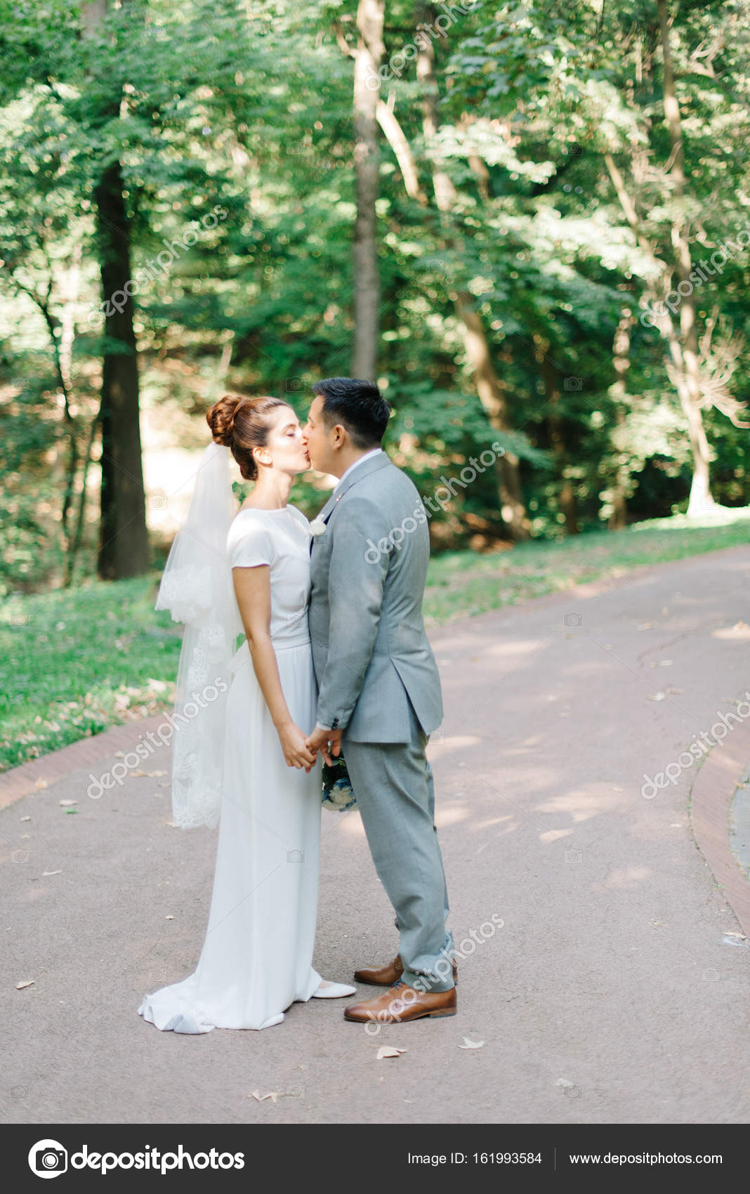 Brunette groom in grey suit kisses bride tender in bright summer ...