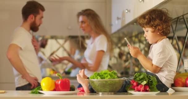 Detail boku portrét malého chlapce hrát s mobilním telefonem a sedí na kuchyňský nábytek se zeleninou na pozadí dohadovat rodičů.
