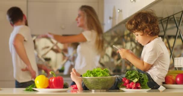 Na pozadí dohadovat rodičů, matka se plácat otce, zatímco malé dítě s mobilním telefonem v ruce sedí na kuchyňský nábytek v přední.