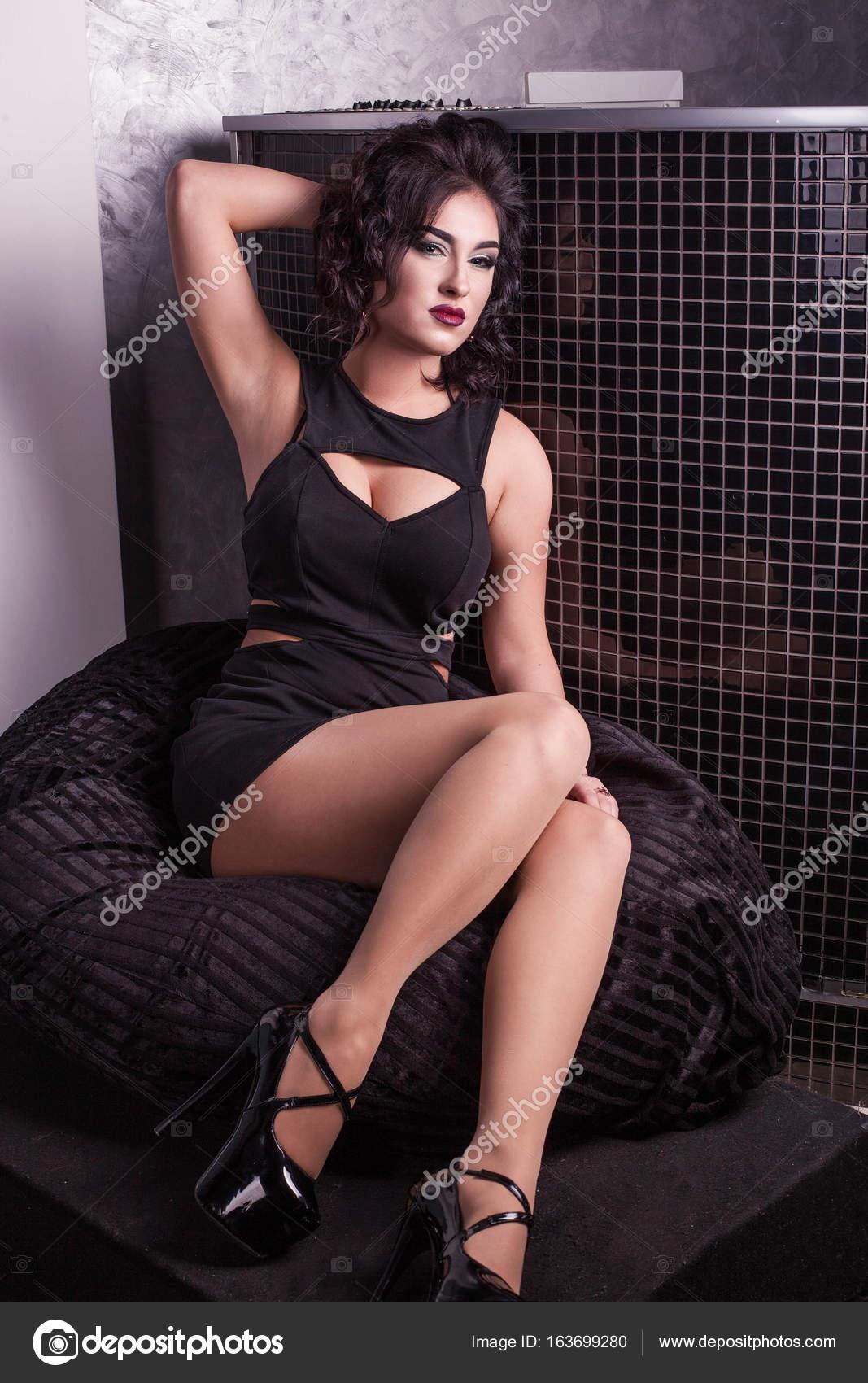7f63931e09a1 Ragazza sexy in un abito corto nero in posa per la macchina fotografica.  Donna che indossa alte colline– immagine stock
