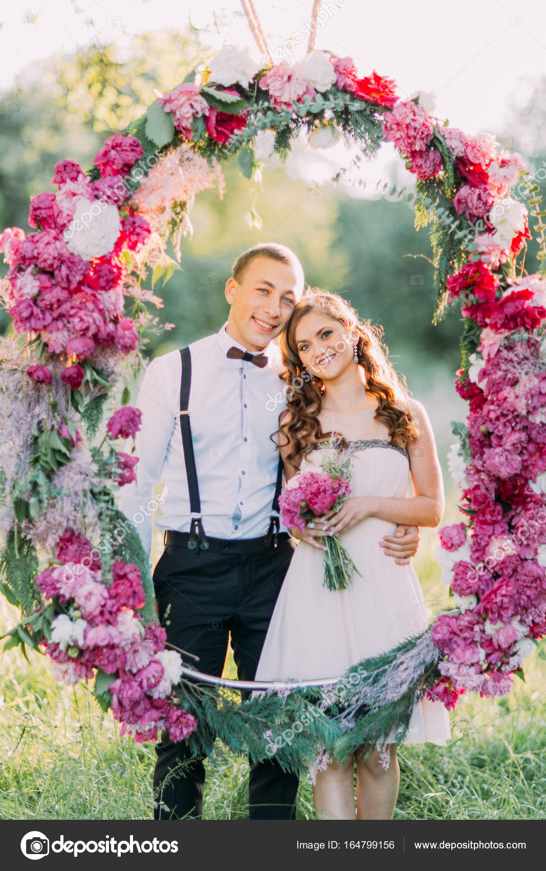 Close up portrait of the beautiful bridesmaid with the flowers and close up portrait of the beautiful bridesmaid with the flowers and the best man in the dark suit hugging behind the big wedding arch made of pink flowers izmirmasajfo Gallery