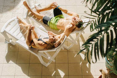 sexy young couple relaxing on sun beds near pool. Girl and guy on summer holidays vacation. Perfect bodies, amazing curves, sunset