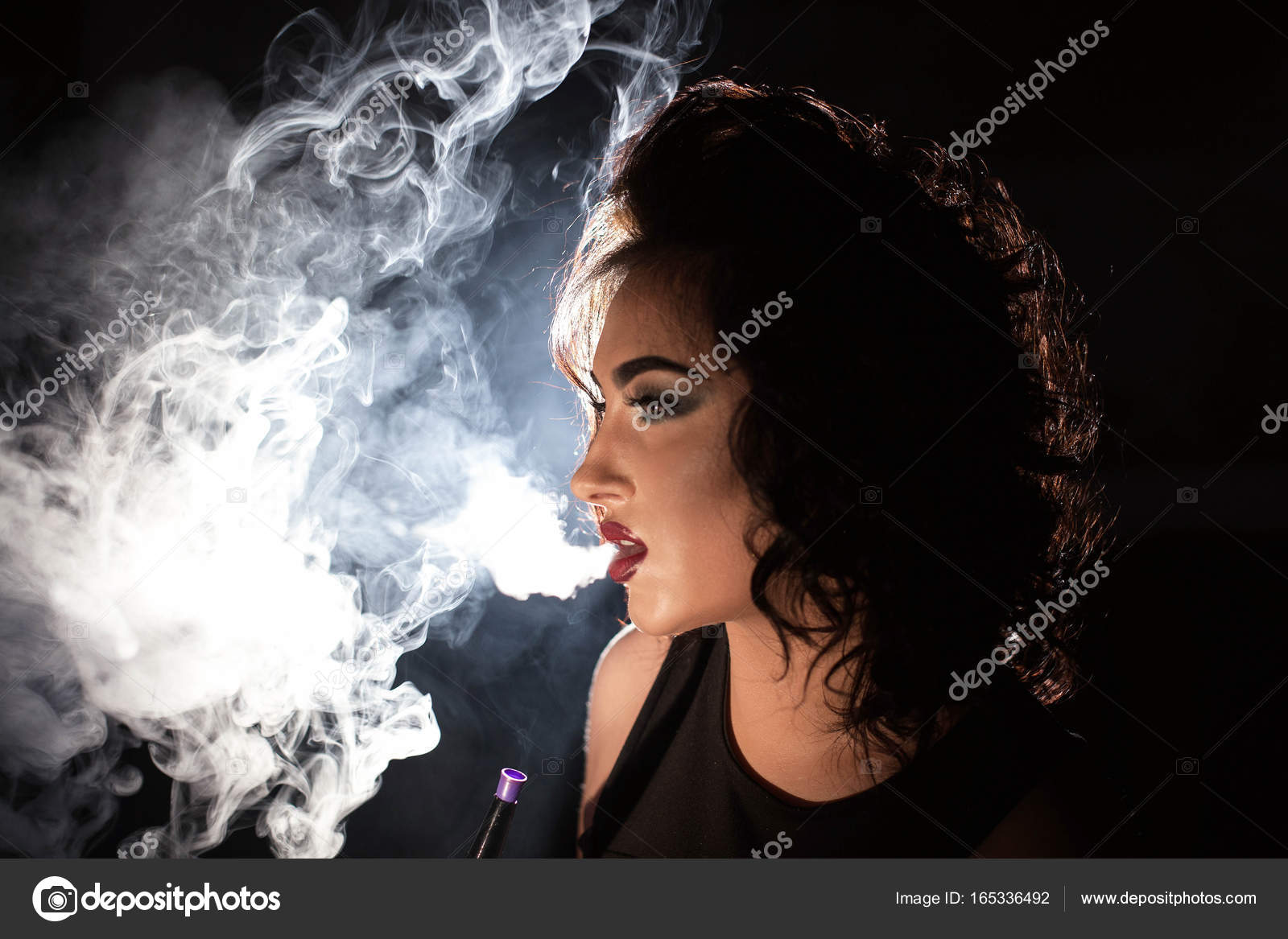 Sexy brunette exhaling hookah smoke and posing for camera