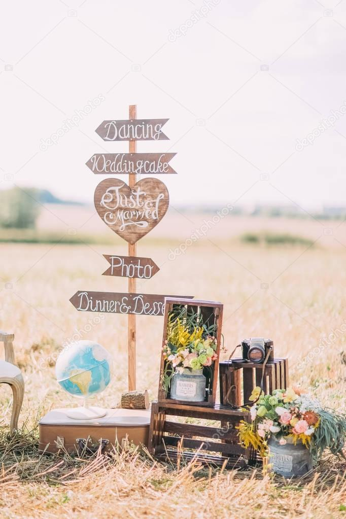 The vertical photo of the wooden plaques with the signs Wedding, photo, dancing placed near the wooden boxes with flowers, old camera and globe in the sunny field.