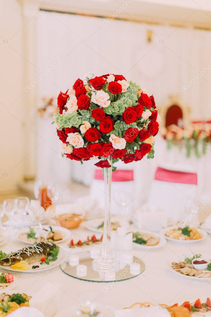 Huge bouquet of red and white roses as a decor of the wedding table set.