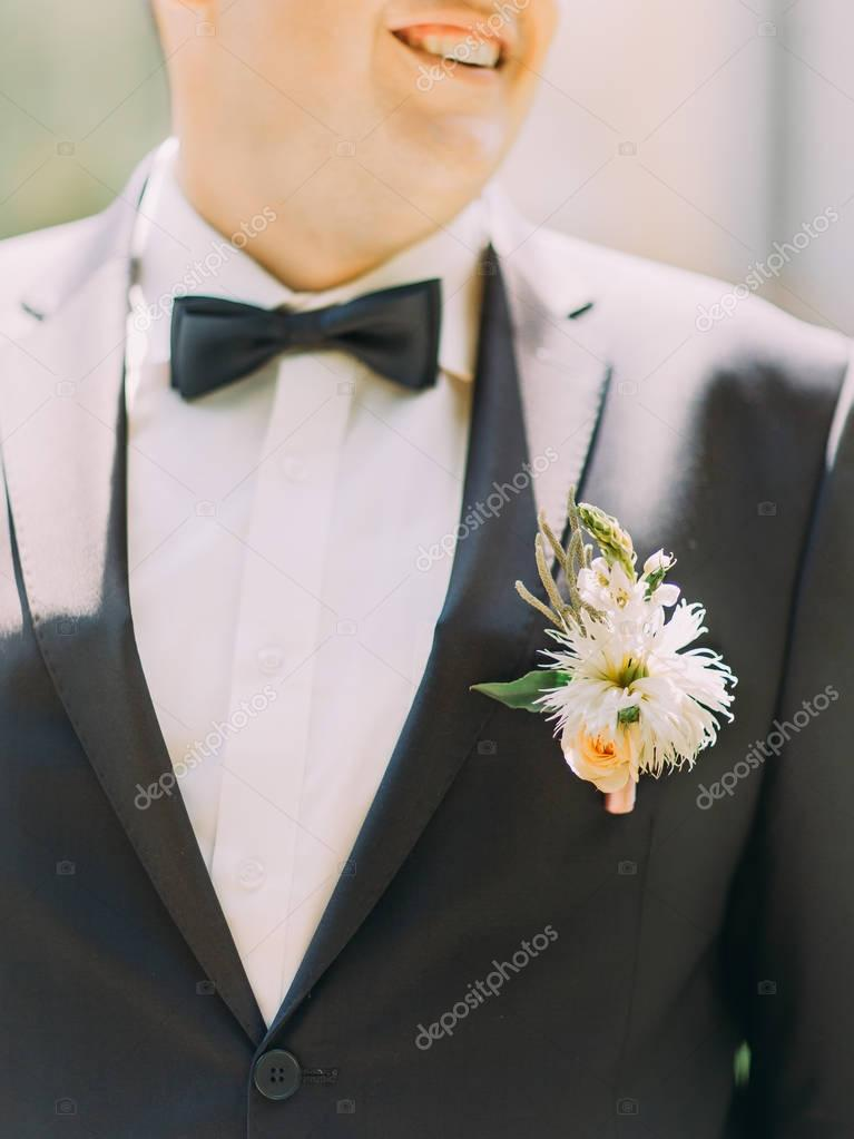 Lovely boutonniere of exotic flowers on the jacket of the groom.