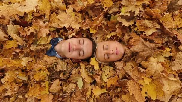 Joyful man and woman lie under fallen leaves in park