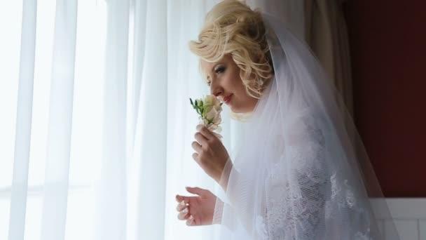 Szőke menyasszony szaga boutonniere állt az ablak előtt