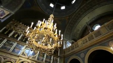 Chandlier with candles hangs from the ceiling in old church