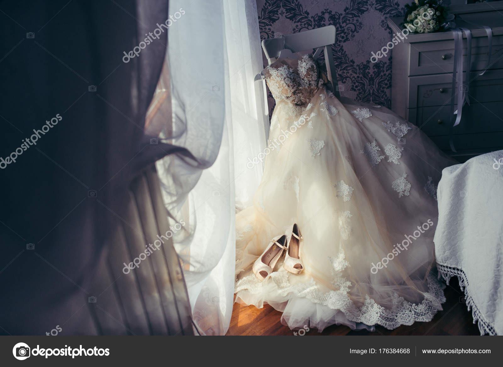 El vestido de novia largo hermoso están colgando en la silla blanca ...
