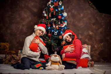 Happy future parents in Santa Claus hats are sitting on the plaid and hugging the pillows at the background of the Christmas tree.