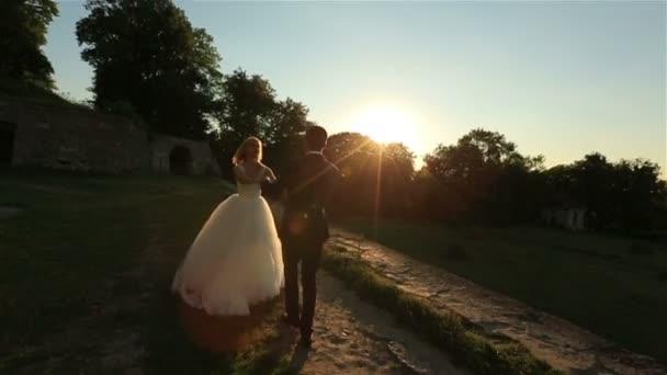 Schöne Hochzeitspaar küssen sanft im Wald. Schöner Sonnenuntergang im Hintergrund. Charmante moment