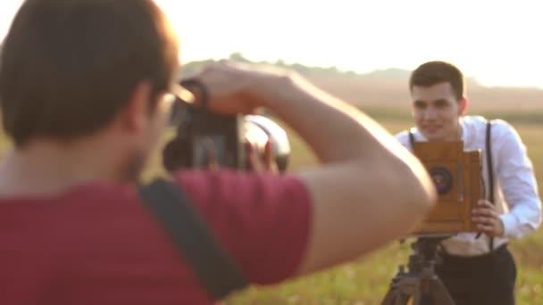 A hátsó nézet a fotós fotózni a vintage öltözött vőlegény a régi kamera. Területi elhelyezkedése.