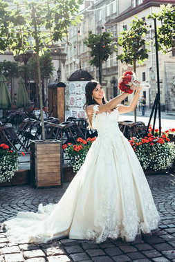 Portrait of the charming brunette with lovely smile raising up the wedding bouquet of red and pink flowers in the sunny street.