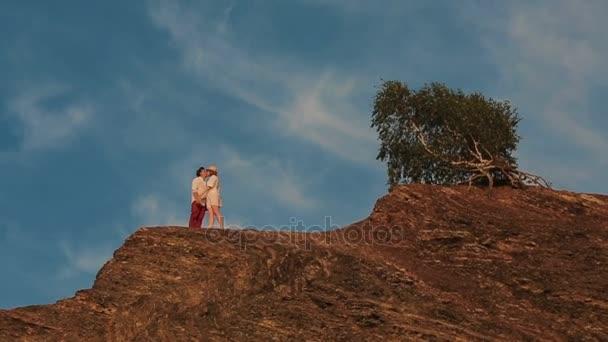 Pohled z brumlat milující pár líbání na vrcholové skále.