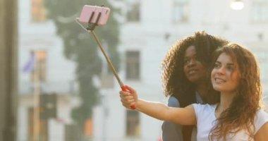 Boční pohled veselá krásné mnohonárodnostní přítelkyně dělat legrační obličeje při pořizování fotografií pomocí selfie stick