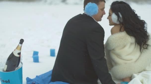 Zpět detailní pohled šťastné krásné novomanželé během jejich svatební zimní piknik v modré barvě. Ženich je něžně líbat svou nevěstu do čela.